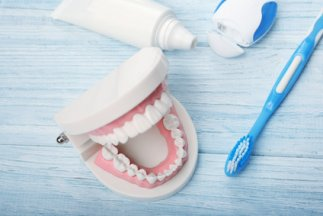 Dental-jaw-model-and-tooth-brush-with-paste-on-wooden-background.jpg